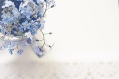 Bouquet des myosotis des marais bleus dans une tasse sur un plateau de dentelle, la vue supérieure Image stock