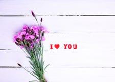 Bouquet des oeillets et de l'inscription roses de champ je t'aime Photos stock