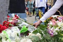 Bouquet des oeillets rouges dans la main de l'homme aux célébrations de Victory Day Image stock