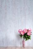Bouquet des pivoines dans un vase contre un mur bleu. Image stock