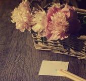 Bouquet des pivoines roses dans un panier et des crayons avec le papier Photographie stock libre de droits