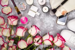 Bouquet des roses avec des cosmétiques dans le parfum, le téléphone et des espadrilles sur un fond gris avec l'espace de copie Photo libre de droits