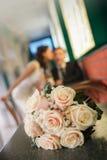 Bouquet des roses beiges et d'un baiser du marié et de la jeune mariée sur un fond Photographie stock