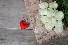 Bouquet des roses blanches avec le coeur rouge sur le fond en bois Photo libre de droits
