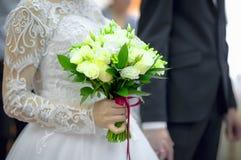 Bouquet des roses dans les mains de la jeune mariée avec la profondeur du champ Photographie stock libre de droits