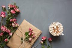 Bouquet des roses roses de buisson, du cadeau pour des femmes et de la tasse de café sur le fond gris chic minable, point de vue  Photos stock