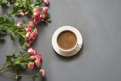 Bouquet des roses de buisson et de la tasse de café roses sur le fond gris chic minable, point de vue supérieure Photographie stock libre de droits