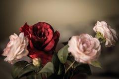 Bouquet des roses de fleurs, roses et rouges de tissu sur un fond foncé Photographie stock libre de droits