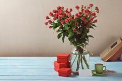 Bouquet des roses, des cadeaux, de la tasse de café et de la carte Photos stock