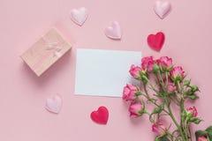 Bouquet des roses, du boîte-cadeau et des coeurs avec la carte de papier blanc sur a Images stock