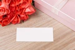 Bouquet des roses, du cadeau et de la carte de voeux rouge-rose sur un fond en bois Images stock