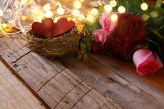 Bouquet des roses et couples des coeurs rouges dans le nid Photographie stock libre de droits