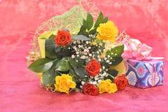 Bouquet des roses et d'un cadeau Image stock