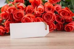 Bouquet des roses et de la carte de voeux rouge-rose sur un fond en bois Photographie stock libre de droits