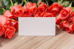 Bouquet des roses et de la carte de voeux rouge-rose sur un fond en bois Image stock