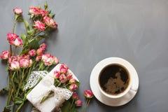 Bouquet des roses et de la tasse de café roses sur le fond gris Carte romantique avec amour Copiez l'espace Vue de ci-avant Image stock