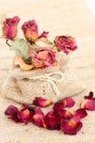 Bouquet des roses et des pétales défraîchis secs au-dessus de la toile à sac de vintage Photographie stock