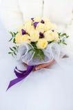 Bouquet des roses et des rubans pourpres dans les mains de la jeune mariée Images stock