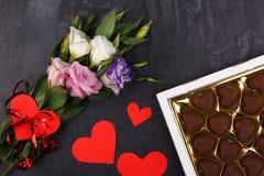 Bouquet des roses japonaises et d'une boîte de chocolats sur un fond en pierre Photographie stock libre de droits