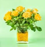 Bouquet des roses jaunes dans un vase décoratif d'isolement sur le fond clair image libre de droits