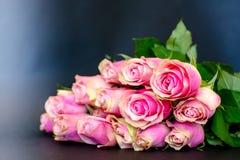 Bouquet des roses roses sur un fond noir Photos stock