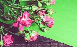 Bouquet des roses roses sur une feuille de papier verte Images stock
