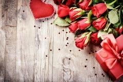 Bouquet des roses rouges avec le coeur et le présent décoratifs St Valen Photographie stock