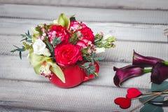 Bouquet des roses rouges dans le vase, coeurs, callas sur la table, l'espace pour le texte Photo stock