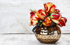 Bouquet des roses rouges dans le vase en verre. Fond en bois blanc Images stock