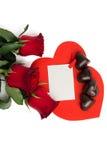 Bouquet des roses rouges, de deux coeurs de papier rouges et des sucreries Images stock