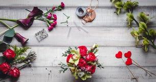 Bouquet des roses rouges, des coeurs, des callas, des oeillets et des rubans sur la table Images stock