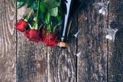 Bouquet des roses rouges, deux verres, bouteille de vin, boîte-cadeau avec l'étiquette sur le panneau en bois de vintage Rose rou Images libres de droits