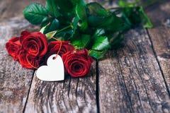 Bouquet des roses rouges, deux verres, bouteille de vin, boîte-cadeau avec l'étiquette sur le panneau en bois de vintage Rose rou Photos libres de droits