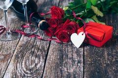 Bouquet des roses rouges, deux verres, bouteille de vin, boîte-cadeau avec l'étiquette sur le panneau en bois de vintage Rose rou Image stock