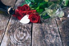 Bouquet des roses rouges, deux verres, bouteille de vin, boîte-cadeau avec l'étiquette sur le panneau en bois de vintage Rose rou Photo stock