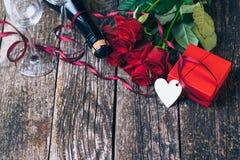 Bouquet des roses rouges, deux verres, bouteille de vin, boîte-cadeau avec l'étiquette sur le panneau en bois de vintage Rose rou Image libre de droits