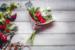 Bouquet des roses rouges et blanches, des coeurs, des callas, des oeillets et des rubans sur la table Photos stock