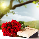 Bouquet des roses rouges et d'un présent Image stock