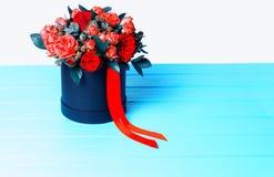Bouquet des roses rouges et du ruban rouge dans une boîte noire circulaire Photo stock