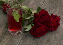 Bouquet des roses rouges et du verre avec la boisson rouge Photo stock