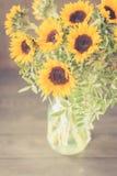 Bouquet des tournesols lumineux dans un pot en verre sur une table en bois Photographie stock libre de droits