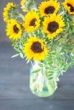 Bouquet des tournesols lumineux dans un pot en verre sur une table en bois Photographie stock