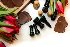 Bouquet des tulipes, des coeurs de chocolat et des échecs rouges Image libre de droits