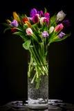 Bouquet des tulipes dans le vase sur l'obscurité Photographie stock