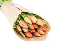 Bouquet des tulipes de couleur de pêche enveloppées en journal de Brown Photographie stock libre de droits