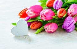 Bouquet des tulipes et du coeur devant la scène de ressort images stock
