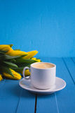 Bouquet des tulipes jaunes et d'un café de tasse Photo stock
