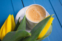 Bouquet des tulipes jaunes et d'un café de tasse Photos stock
