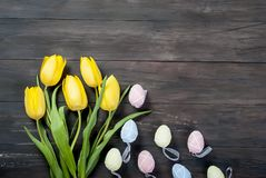Bouquet des tulipes jaunes et des oeufs de pâques colorés sur un CCB en bois Photos libres de droits