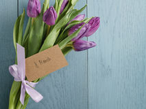 Bouquet des tulipes pourpres attachées avec le ruban sur la table en bois bleue avec la carte de papier pour le 8 mars Image stock